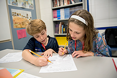 2 students writing with pencils