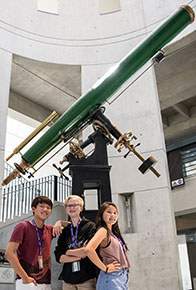 3 cty students standing under a telescope