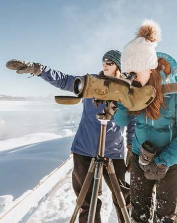 2 participants looking through a scope at the snow