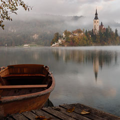 A still lake with a boat in the foreground and mystical castle in the background