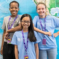 3 CTY students standing in front of a world map